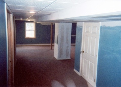 Finished basement main view with ceiling tiles and sheet-rock to conceal ducking vents.