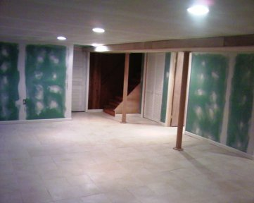 Finished basement with installed tile floor, sheet rock ceiling and walls. The ceiling was with sound proof barrier insulation. we also installed several recessed lights. the underlying plumbing was concealed by a custom-made access door for servicing