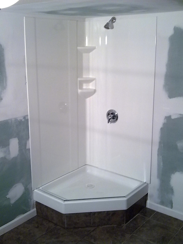 Corner basement shower enclosure.