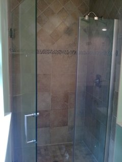 Shower surround with glass doors.